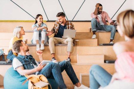 Photo pour Heureux jeunes étudiants passer du temps ensemble au collège sur tribunes en bois - image libre de droit