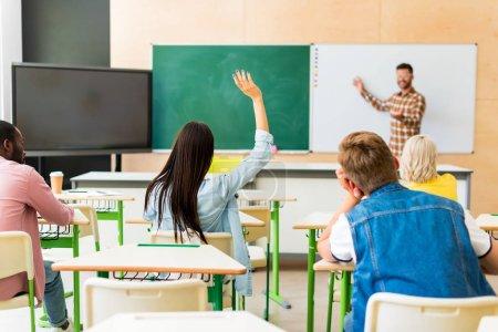 Foto de Vista trasera de jóvenes estudiantes que escuchar conferencias de maestros en el Colegio - Imagen libre de derechos