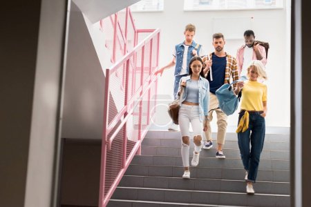 stylish young students walking down on stairs of college corridor