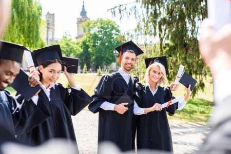 Photo for Young graduated students spending time together in college garden - Royalty Free Image