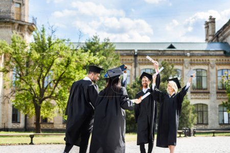 young graduated students with diplomas greeting each other in college garden
