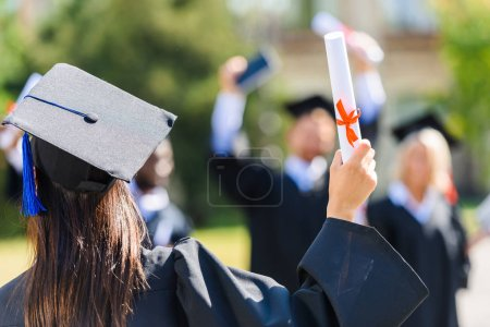 Photo for Rear view of graduated student girl with diploma greeting classmates - Royalty Free Image