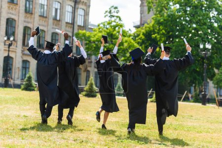Photo for Rear view of celebrating young graduated students in capes walking by university garden - Royalty Free Image