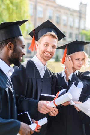 happy multiethnic graduated students in capes with diplomas