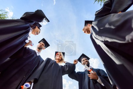 bottom view of happy young graduated students in front of blue sky