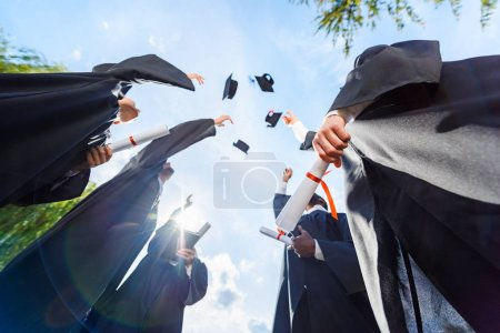 Photo for Bottom view of graduated students throwing up hats in front of blue sky - Royalty Free Image