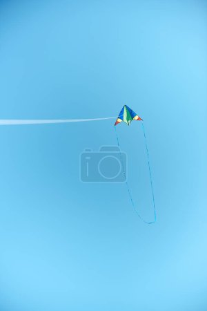 colorful kite flying high in blue clear sky