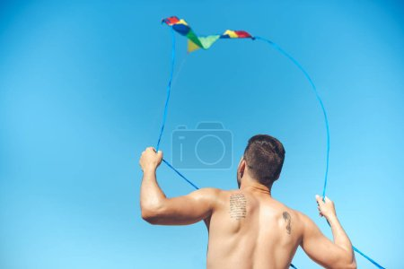back view of man with colorful kite against clear blue sky