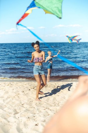 selective focus of multicultural friends with kites spending time on sandy beach together