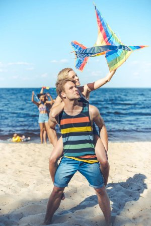selective focus of couple with colorful kite  with multiracial friends behind spending time on sandy beach
