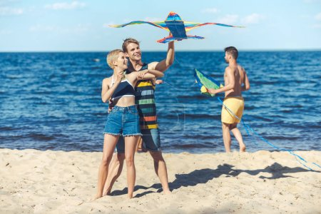 group of young friends with kite spending time on sandy beach together
