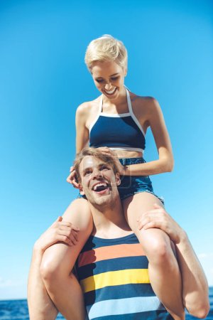 low angle view of young woman sitting on boyfriends shoulders against clear blue sky