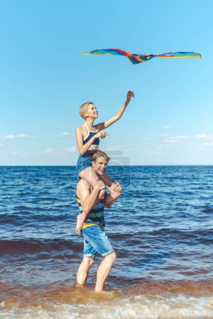 young woman with colorful kite sitting on boyfriends shoulders on beach