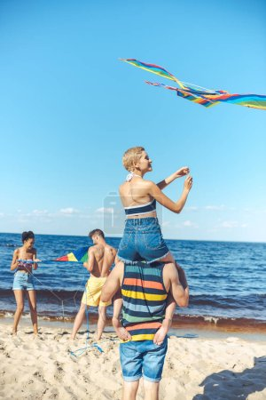 selective focus of interracial group of friends with kites having fun on sandy beach