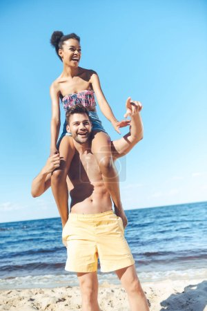 cheerful african american woman sitting on boyfriends shoulders on beach