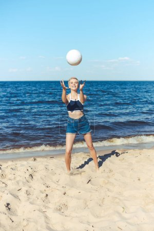 smiling woman catching volleyball ball on beach on summer day