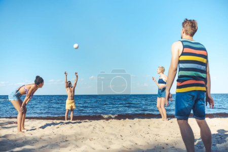 interracial friends playing volleyball together on sandy beach