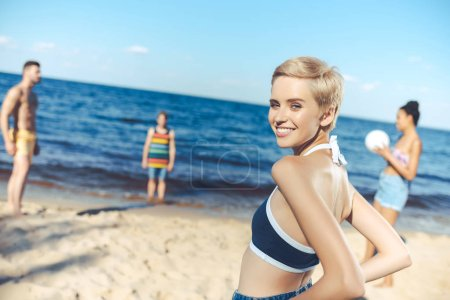 selective focus of smiling woman looking at camera while multicultural friends playing volleyball on beach
