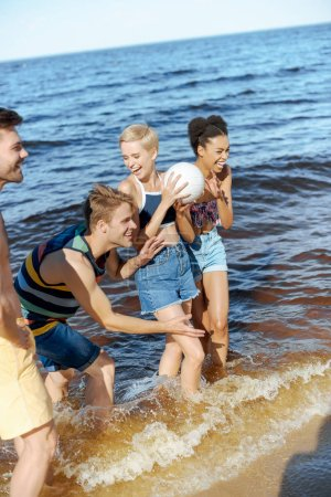 happy interracial group of friends with volleyball ball having fun by sea