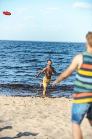 selective focus of young men playing with flying disc on sandy beach