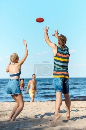 enfoque selectivo de amigos multirraciales jugando con disco volador juntos en la playa