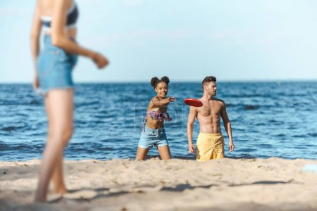 selective focus of interracial friends playing with flying disk on sandy beach