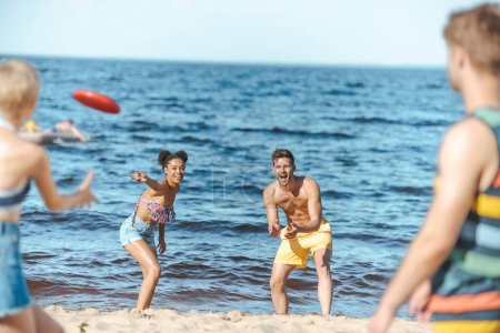selective focus of multiracial friends playing with flying disc together on beach