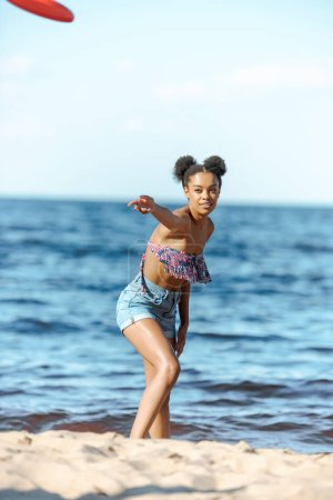 african american woman throwing flying disc on sandy beach
