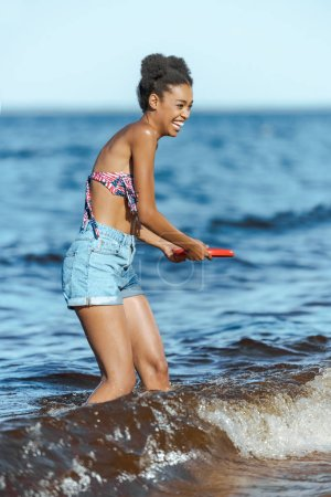 cheerful african american woman with flying disc on beach