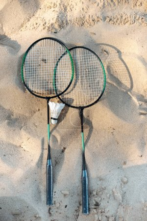 close up view of badminton racquets and shuttlecock lying on sandy beach
