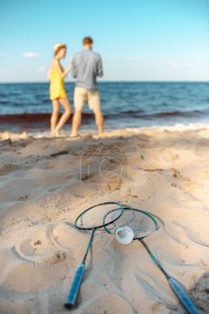 selective focus of badminton equipment and couple on sandy beach