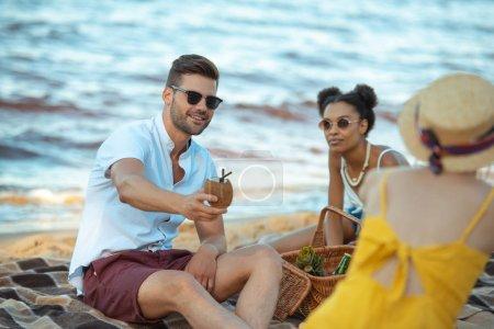 mise au point sélective du groupe d'amis au repos sur la plage de sable ensemble