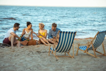 interracial smiling young friends with beer resting on sandy beach together on summer day