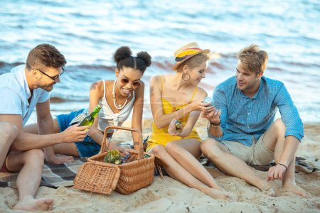 Interracial souriant jeunes amis avec de la bière au repos sur la plage de sable ensemble le jour de l'été