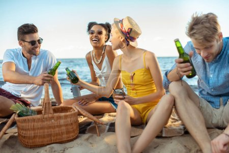 Photo for Interracial smiling young friends with beer resting on sandy beach together on summer day - Royalty Free Image