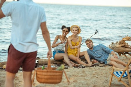 partial view of man with picnic basket and multiethnic friends on sandy beach