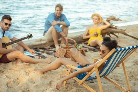 selective focus of multiethnic friends with drinks and acoustic guitar resting on beach together