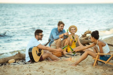 multiethnic smiling friends with drinks and acoustic guitar resting on beach together