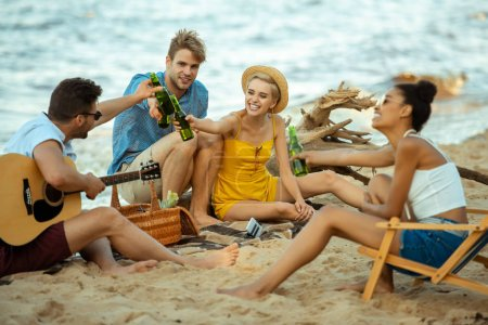 multiethnic happy friends with acoustic guitar clinking drinks while resting on beach together