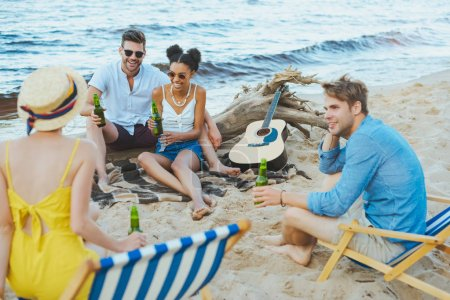 selective focus of multicultural young friends with glass bottles of beer spending time together on sandy beach