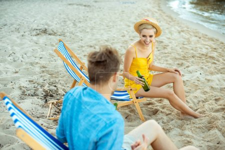 partial view of couple with beer in glass bottles resting in beach chairs on summer day