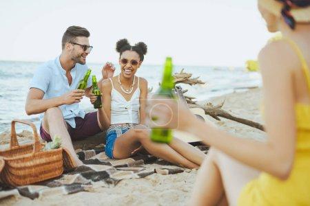mise au point sélective du groupe d'amis avec de la bière au repos sur la plage de sable ensemble