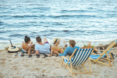 Photo for Back view of multiethnic friends resting on blanket on sandy beach - Royalty Free Image