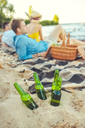 selective focus of glass bottles of beer in sand and interracial young people resting near by
