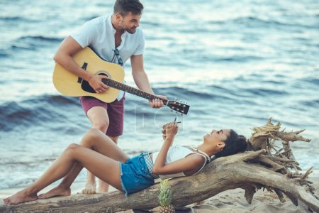 man playing acoustic guitar for african american girlfriend with coconut cocktail on sandy beach