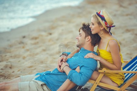 side view of young couple resting on beach on summer day