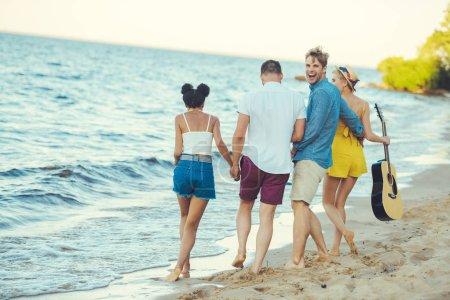 Foto de Grupo multiétnico de amigos con guitarra acústica caminando por el mar - Imagen libre de derechos