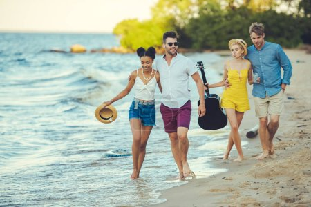 multiethnic group of friends with acoustic guitar walking together by sea