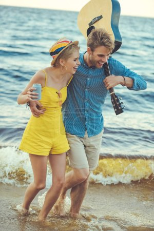 happy couple with soda drink and acoustic guitar walking on beach