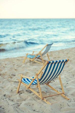foco selectivo de sillas de playa de madera en la playa de arena con el mar en el fondo